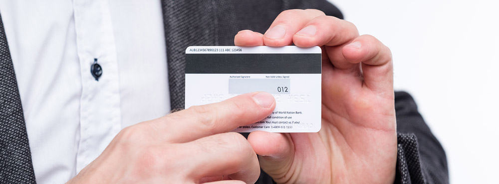 man showing where CVV is located on a credit card