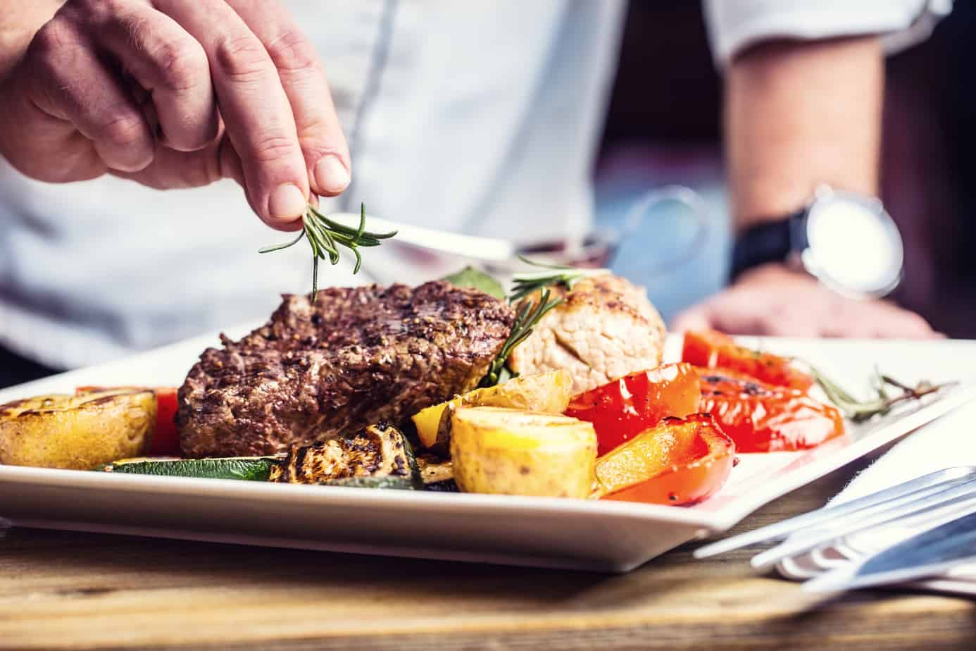 Chef In Hotel Or Restaurant Kitchen Cooking Only Hands Prepared Beef Steak With Vegetable Decoration 81415061