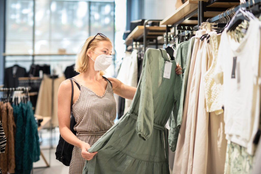 Fashionable Woman Wearing Protective Face Mask Shopping Clothes In Reopen Retail Shopping Store New Normal Lifestyle 196398434