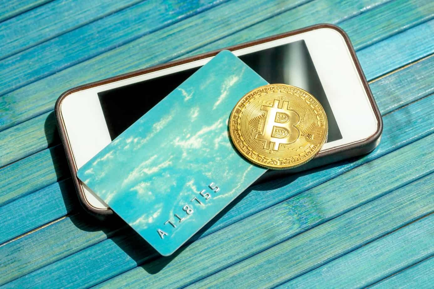 bitcoin gold coin and a gift card credit card laying on top of a modern smartphone screen btc blockchain payments mobile 216994757