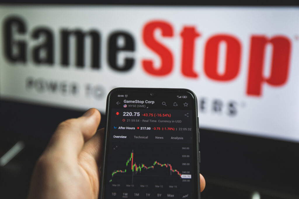 holding mobile phone with stock market charts of gamestop 213526229