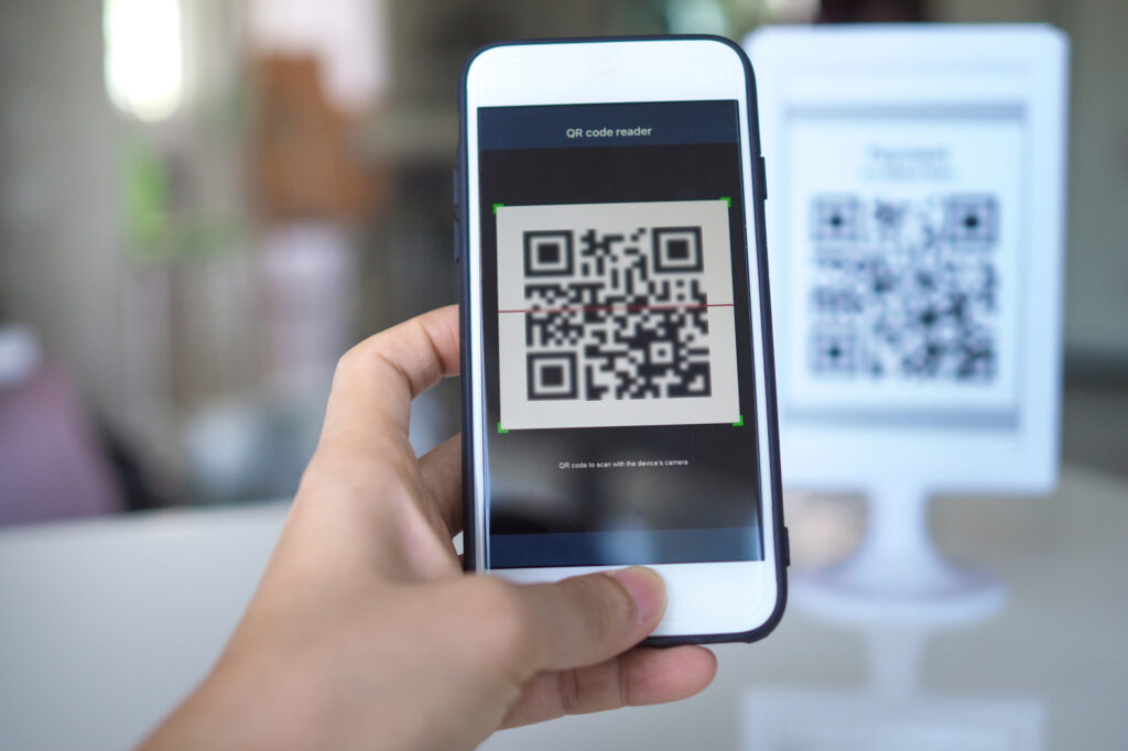 women hand uses a mobile phone application to scan qr codes in stores that accept digital payments without money and plastic 185122541