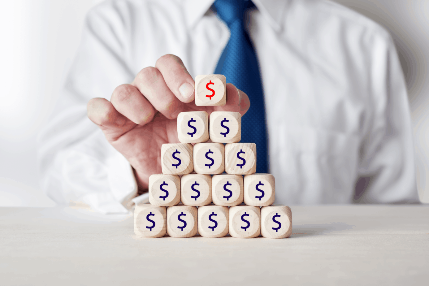 businessman placing a wooden cube with check percent or percentage symbol on top of tiered wooden cubes 218070076