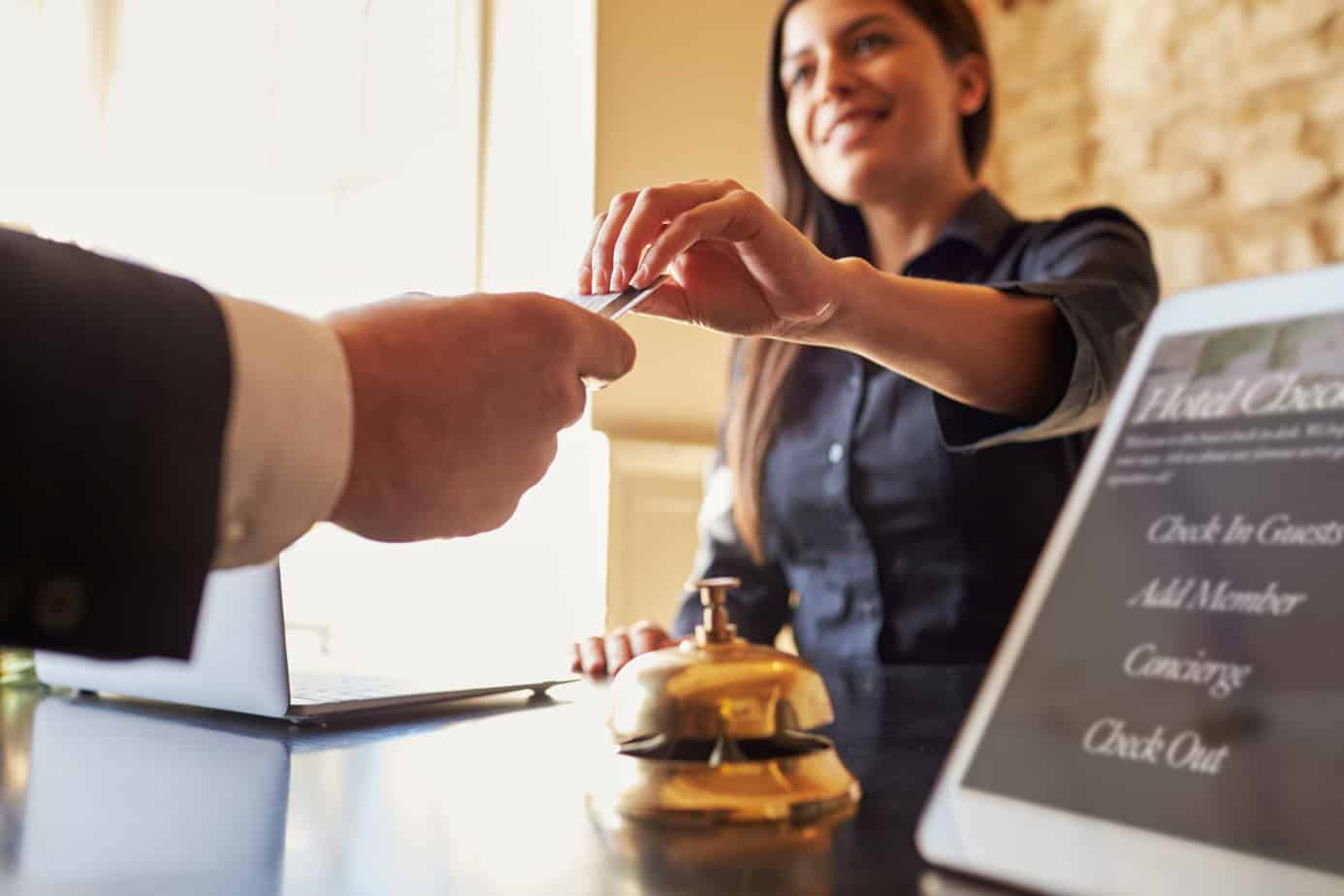 guest takes room key card at check in desk of hotel close up 71533469