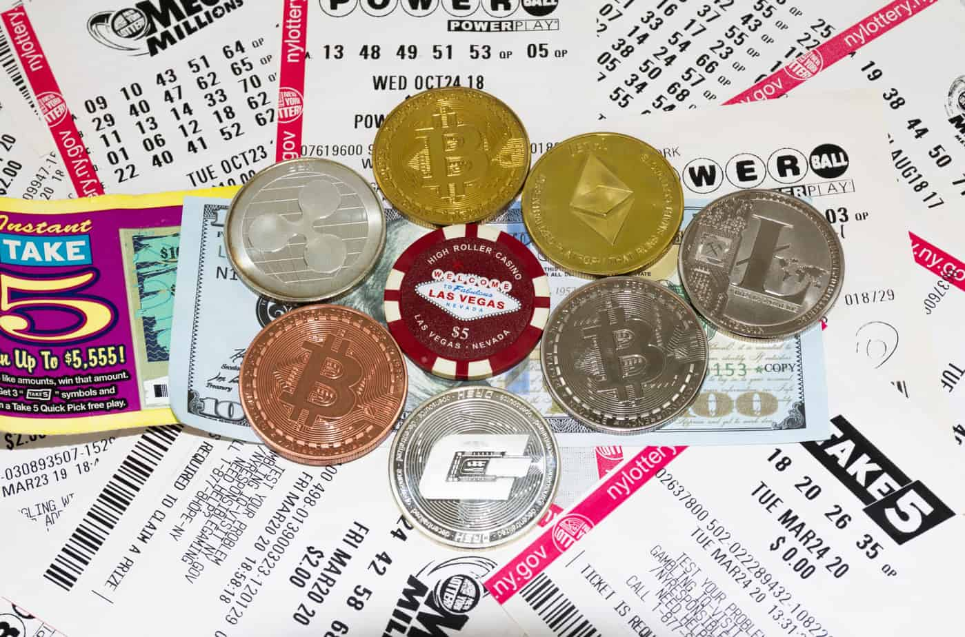 bitcoin ethereum and other cryptocurreny coins on top of lottery tickets and money 219344635