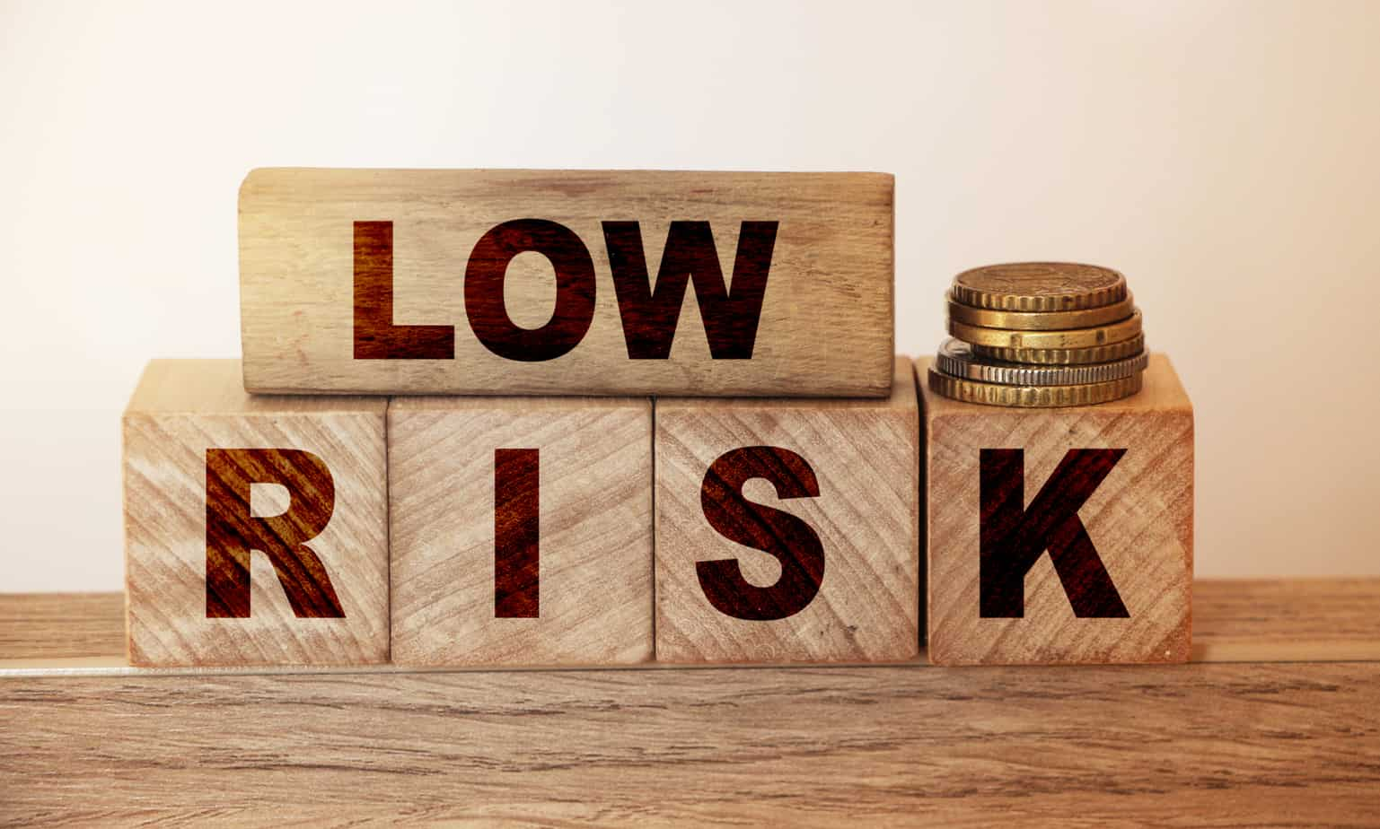 low risk on wooden blocks and coins stack on wooden table rrisk concept in business or investment 191313013