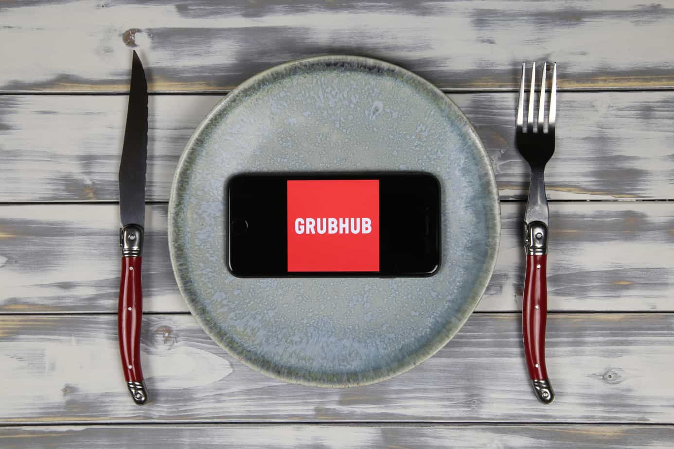close up of mobile phone screen with logo lettering of food delivery service grubhub on wood table with dish and cutlery 205467998
