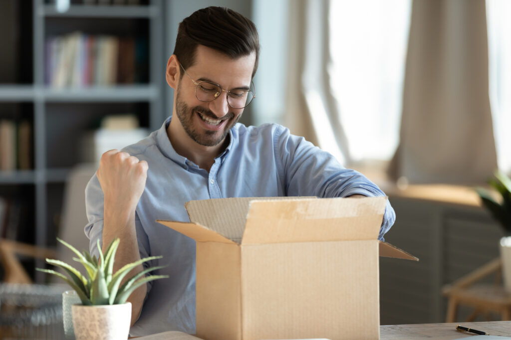happy 30s young man celebrating getting purchase from internet store 207761398